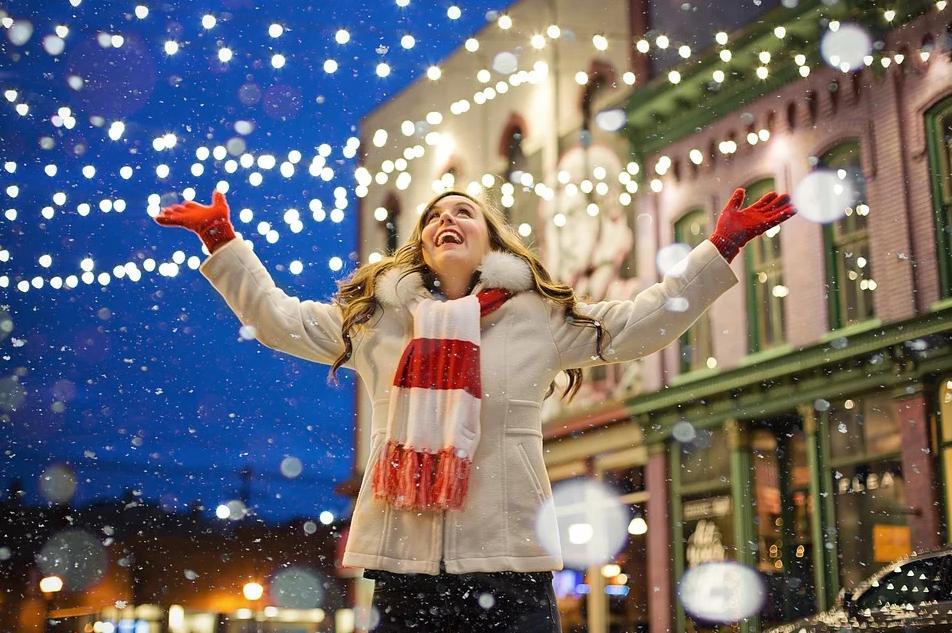 Mujer viendo bajar la nieve en la calle decorada de Navidad