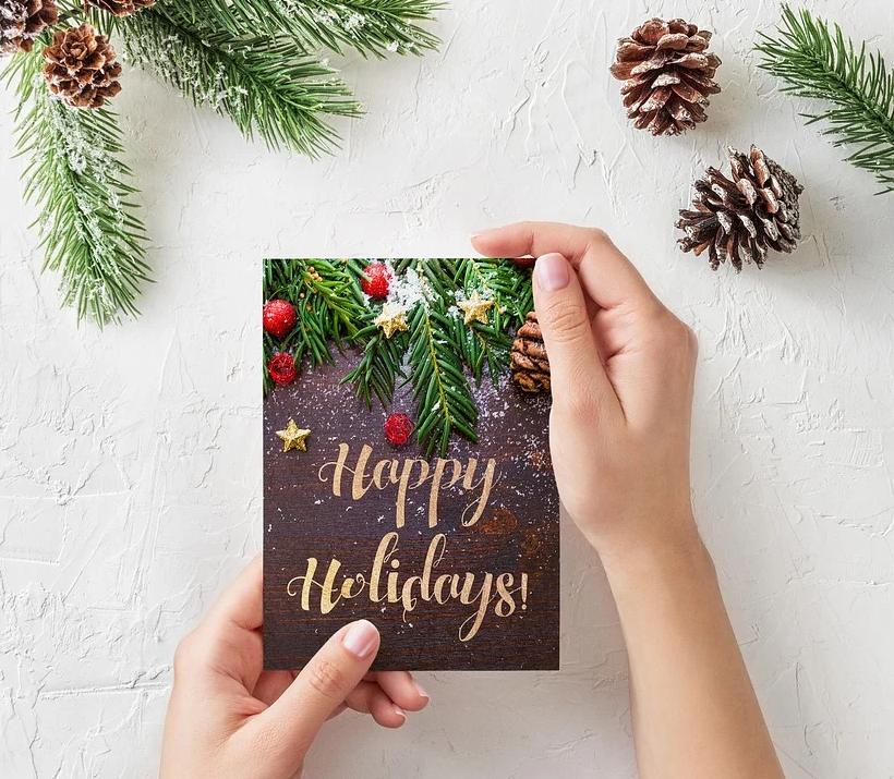 Imagen de unas manos mostrando una postal de Navidad que pone Happy Holidays